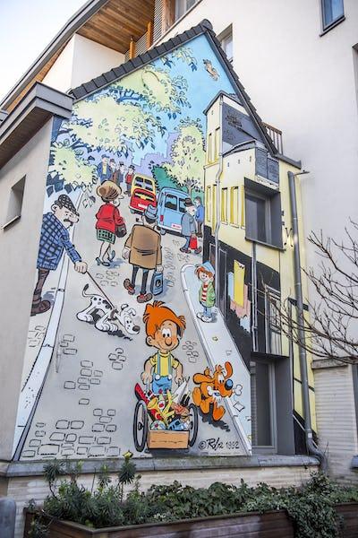Stripmuren, street art, herwerkte straatnaamborden te voet